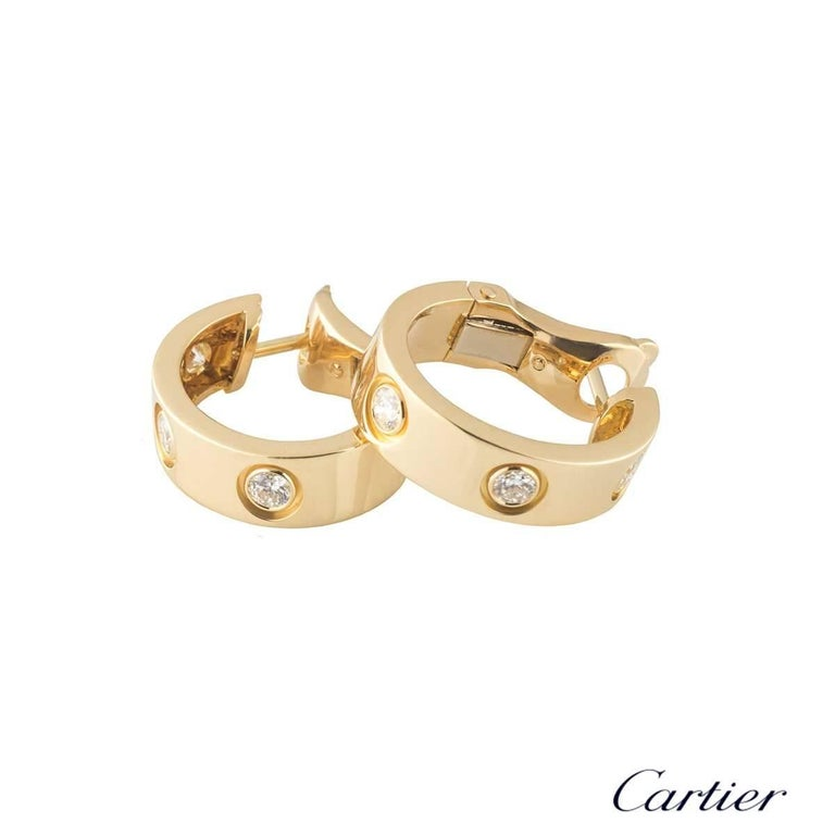 A pair of 18k yellow gold diamond earrings from the iconic Love collection by Cartier. Each hoop earring is set with 3 round brilliant cut diamonds. The earrings are 18mm in length and 5mm in width and feature a post and lever hinged fittings. The