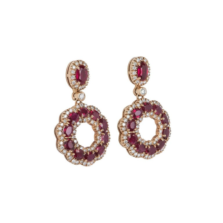 A stunning pair of 18k rose gold ruby and diamond earrings. The earrings feature a single ruby with pave set round brilliant cut diamonds around it followed by a single diamond, suspended from it is an open work circular motif set with oval shaped