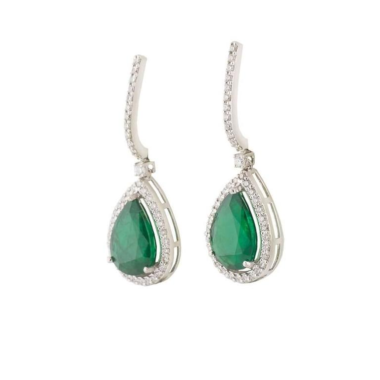 A pair of 18k white gold emerald and diamond drop earrings. The earrings are each set to the centre with a pear shaped emerald totalling 7.57ct dispersing a vibrant green hue throughout, set in a three claw setting. Accentuating the emeralds are a