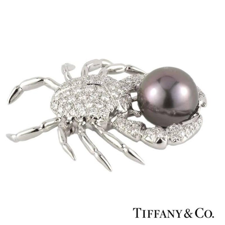 An exquisite diamond and pearl crab brooch in platinum by Tiffany & Co. The open work crab brooch is comprised of round brilliant cut diamonds pave set throughout the body and claws totalling approximately 2.70ct, predominantly G colour and VS