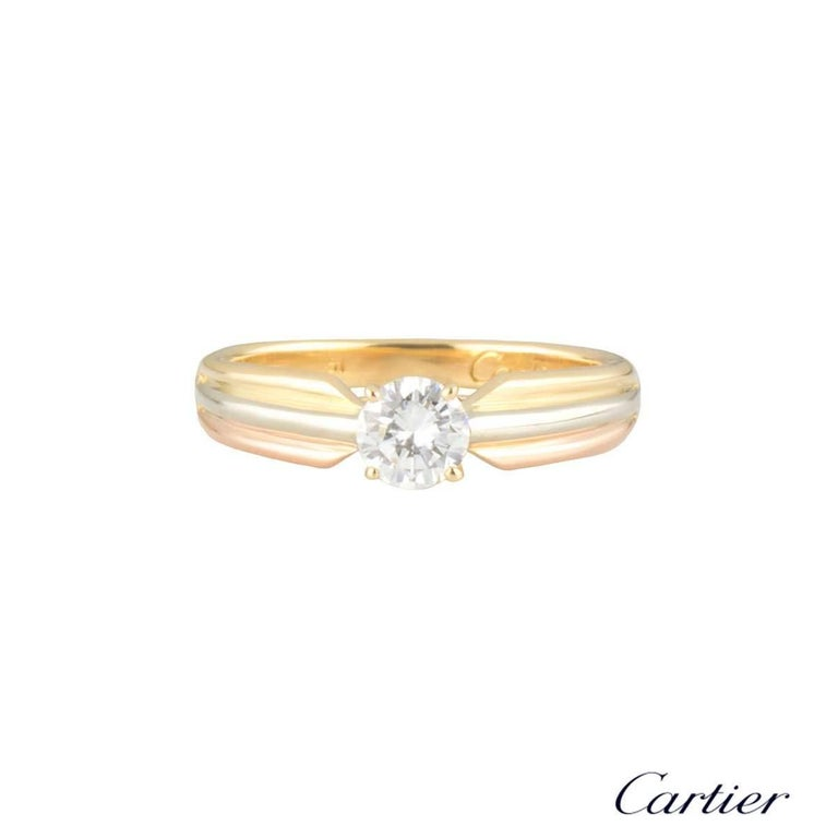 An 18k tri-colour gold diamond ring from the Trinity de Cartier collection. The ring is set to the centre with a 0.32ct round brilliant cut diamond, D colour and VVS2 in clarity. The diamond is set within a classic 4 claw setting with the band