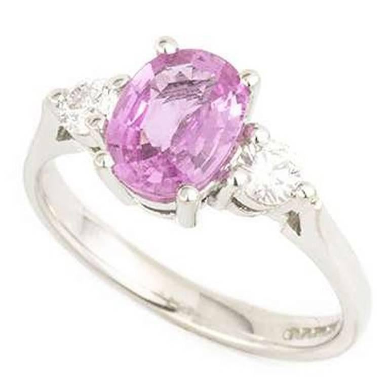 A gorgeous 3 stone pink sapphire and diamond ring in 18k white gold. The ring is centred with an oval cut pink sapphire weighing approximately 1.25ct. The stone is set between 2 round brilliant cut diamonds with a total diamond weight of 0.26ct, the