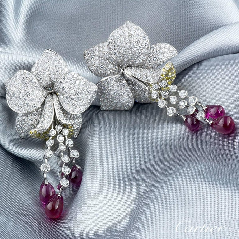 A luxurious and extremely rare pair of platinum Cartier earrings from the Caresse D' Orchidees collection. Each earring comprises of an Orchid motif with 5 petals embellished with round brilliant cut diamonds. The lip of the orchid is detailed with