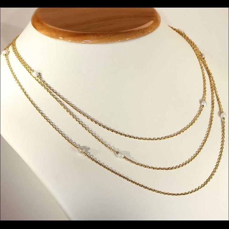 This antique Victorian link chain was handcrafted in 14 karat gold. It features 9 gray naturals pearls that range in diameter from 3.3 mm to 7 mm. There are three total chains on this one of a kind necklace. The shortest chain measures 18 ¼ inches