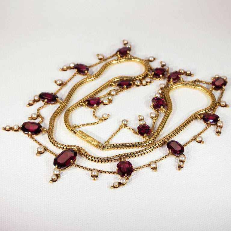 This breathtaking Victorian garnet and pearl gold necklace was handcrafted in England around 1850-60 and comes inside its original fitted box. The double chain measures 16.25 inches in length and is made up of a snake chain with a looping link