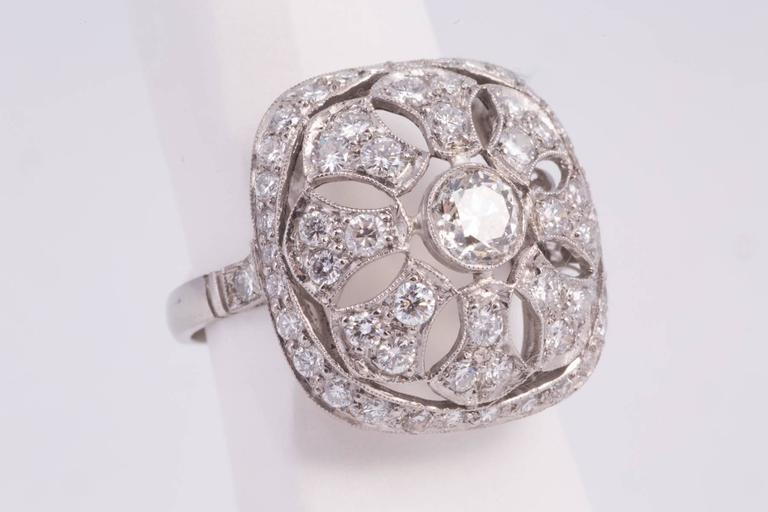 Antique european cut diamond filigree ring. The center is approx. .75ct, has G-H color and SI clarity. It is surrounded by 20 single cut round diamonds weighing approx. 1.00cts. The mounting is Platinum. Circa. 1940.