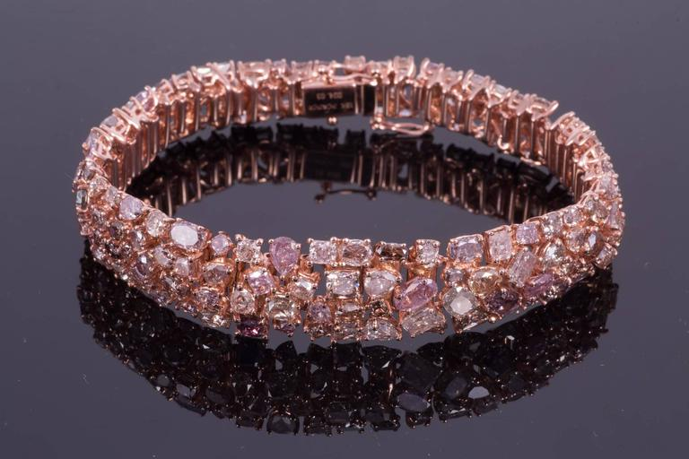 Absolutely breathtaking pink diamond bracelet. The bracelet is made up of 24.03cts of different fancy cut diamond shapes. Though the diamonds are predominately pink, there are other colors such as purple, blue, green, yellow gray and white. The
