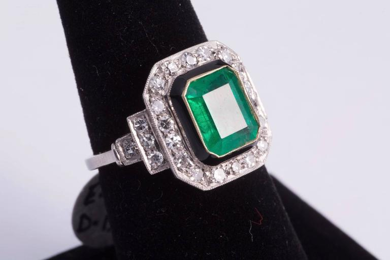 Gorgeous, natural, approx. 2.50ct emerald cut emerald in the center of the ring. The center stone is bezel set in gold and had a black enamel border. Stepping down from the enamel there are a total of 26 diamonds around and diamonds on the sides of
