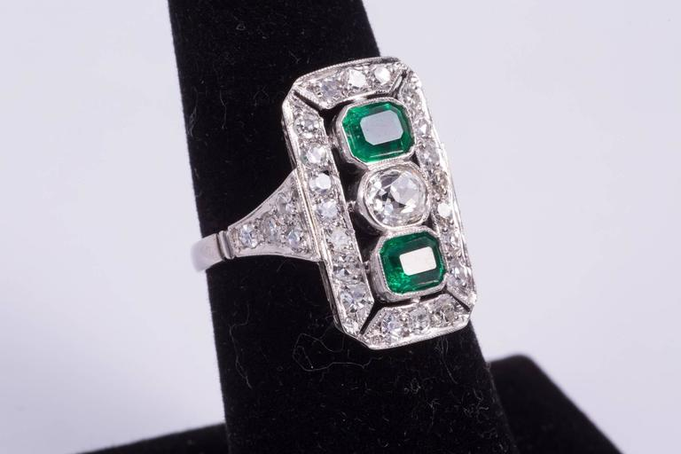 Emerald and diamond ring with two emeralds that weigh approx. 1.00cts total. The emeralds have wonderful rich green color. The diamond in the center is an approx. .50ct antique cushion cut diamond and has G-H color and VS2-SI1 clarity. There are 28