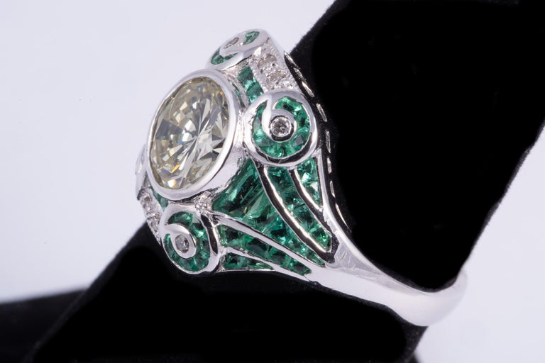 This ring features and 1.41ct natural yellow round brilliant cut diamond. The ring is accented by calibre cut emeralds and full cut diamonds weighing approx. .05cts. Set in platinum, 6.00grams. Size 6.5 and is sizable.