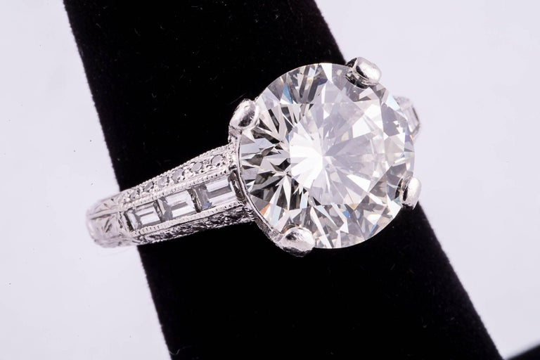 One round brilliant cut diamond weighing 4.04cts set in a gorgeous platinum and diamond mounting. The center diamond has K Color and VS2 Clarity. The diamond was graded by GIA  and is very white and lively. There are 6 rectangular baguette diamonds