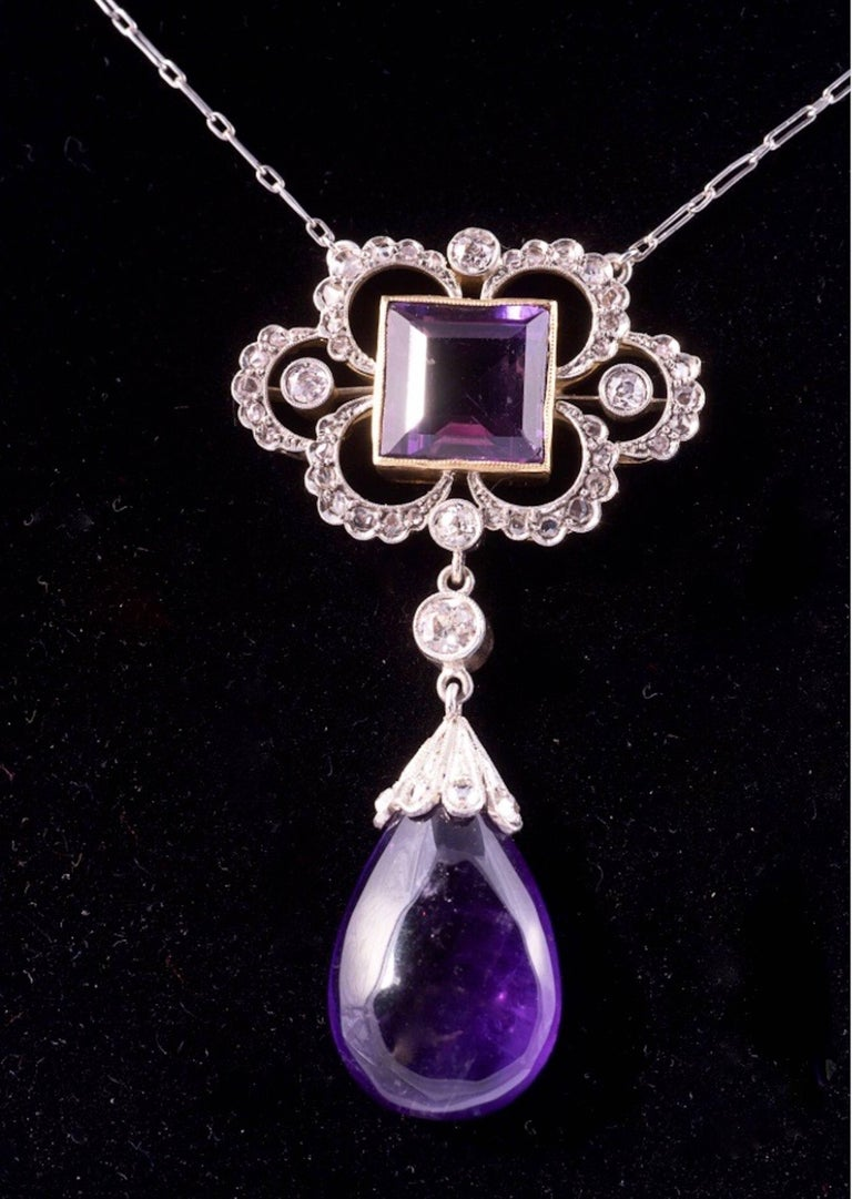 Breathtaking Edwardian Amethyst and Diamond Pendant necklace. The design features a 9.50mm square step cut amethyst and a an approximate 1 inch drop shape amethyst. There is one .20ct diamond, four .10ct diamonds and 42 smaller diamonds in the