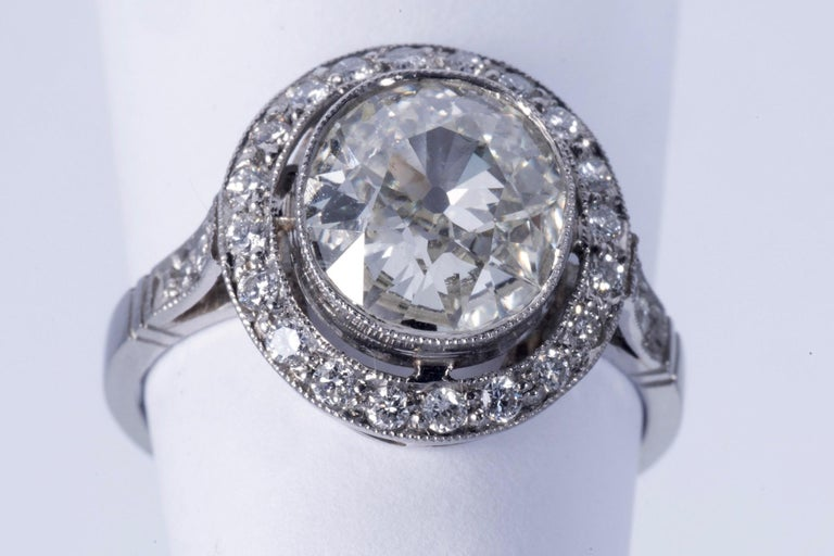 Fabulous European cushion cut diamond. The diamond weighs approx. 2.00cts and has J-K color and SI1 clarity. There is a halo with approx. 20 round cut diamonds and there are 2 round cut diamonds on either side of the shank. All together, the side