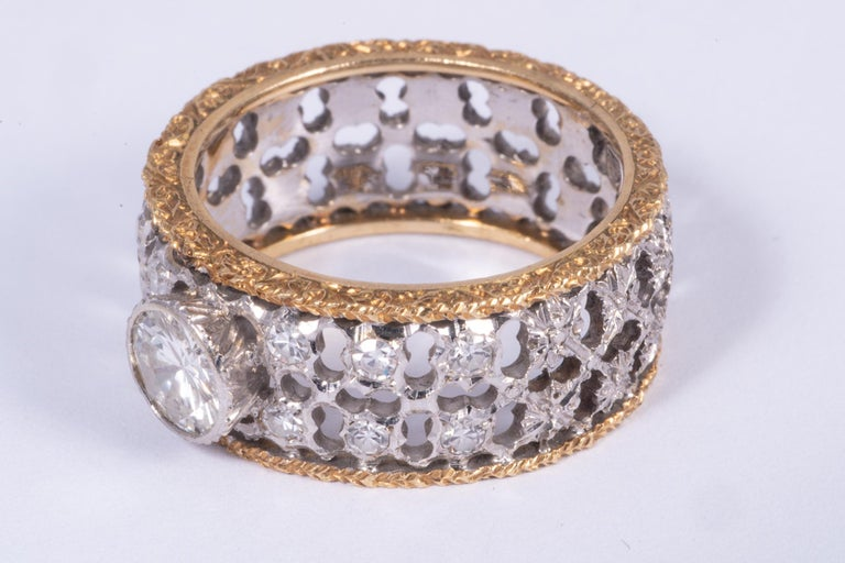 Signed Mario Buccellati ring with a center diamond. The diamond weighs approximately .75cts and measures 5.8x5.8x3.4mm. The diamond has F-G color and VS clarity. There are 6 single cut diamonds on either side of the ring totaling 12 diamonds. These