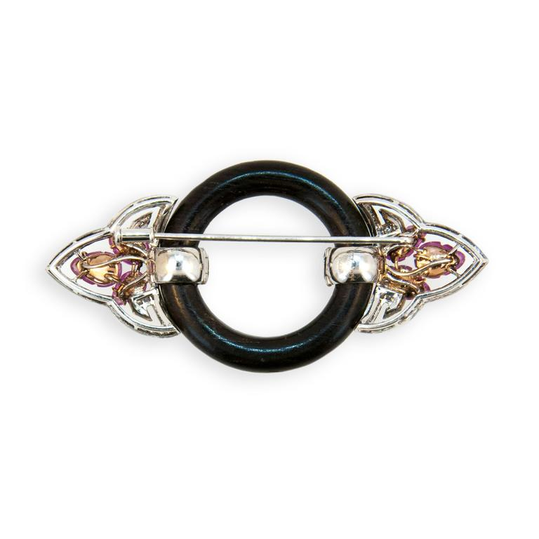18 karat blackened rose and white gold brooch. Dark wood circle (6) Pink Sapphire leaf cut 6.05 carats total weight (42) round Pink Sapphires 1.25 carats total weight and (90) round Diamonds 1.00 carats total weight