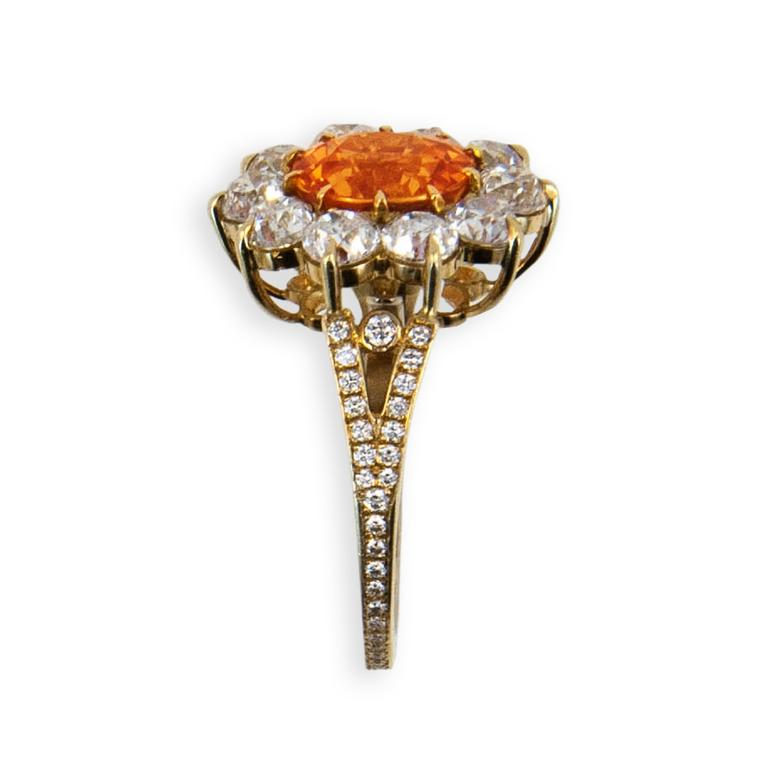 18 karat yellow gold ring set with one slightly ovalish faceted antique style cut Mandarin Garnet 4.47 carats total weight (10) 3.6 mm Mine cut Diamonds 3.04 carats total weight and (58) .9 to 1.5 mm round Diamonds .25 carat total weight Size 6 3/4