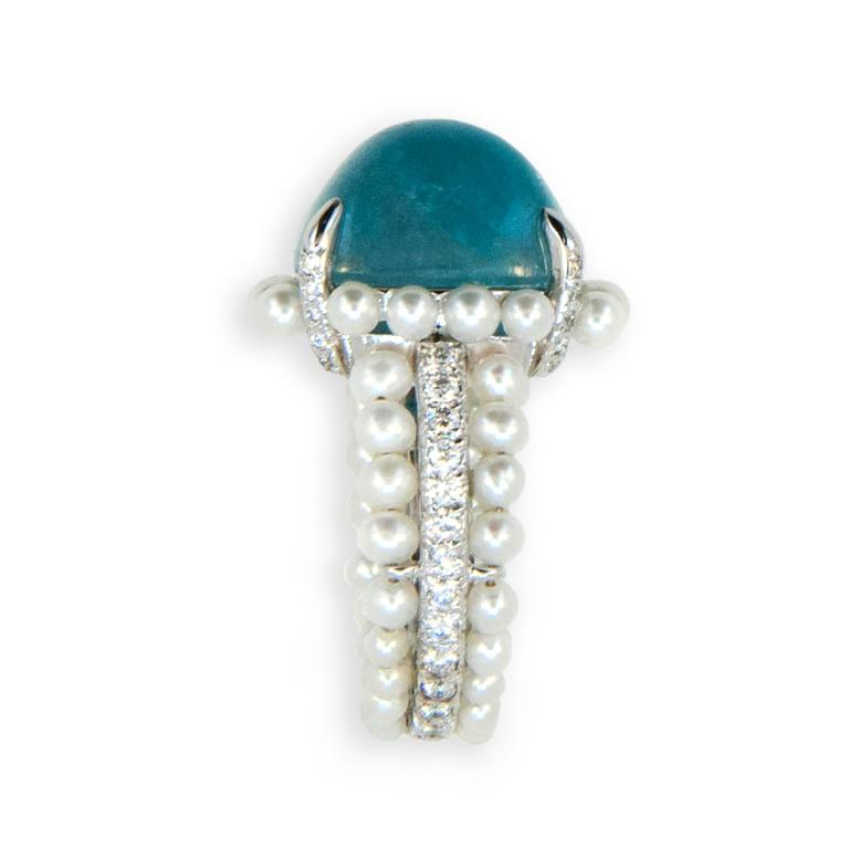 18 karat white gold ring set with one cabochon antique cushion cut Paraiba Tourmaline 11.99 carats (54) cultured Pearls are set surrounding Paraiba at base and in two outer rows of shank (51) round Diamonds are set on four prongs and in center row