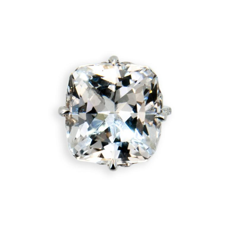 18 karat white gold ring set with one faceted pillow cut Topaz very light grey color 27.99 carats. Flower motif on sides of basket set with (4) round Blue Sapphires .32 carat total weight. Basket prongs and 1.6 mm shank are set with 104 round