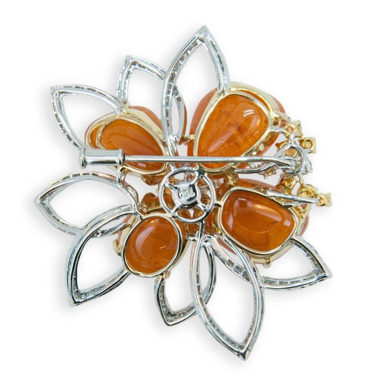 18 karat yellow and white gold brooch with Mandarin Garnet 63.09 carats total weight. Ten Yellow and Orange Sapphires 0.82 carats total weight. 112 Round diamonds 1.47 carats total weight.