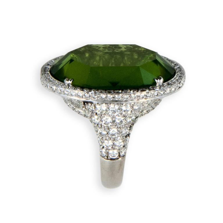 18 karat white gold ring set with one oval faceted Peridot 27.44 carats, no culet, table like facet on both sides. Bezel, under bezel and partial shank are pave'  and microset with 222 diamonds 2.87 carats total weight.