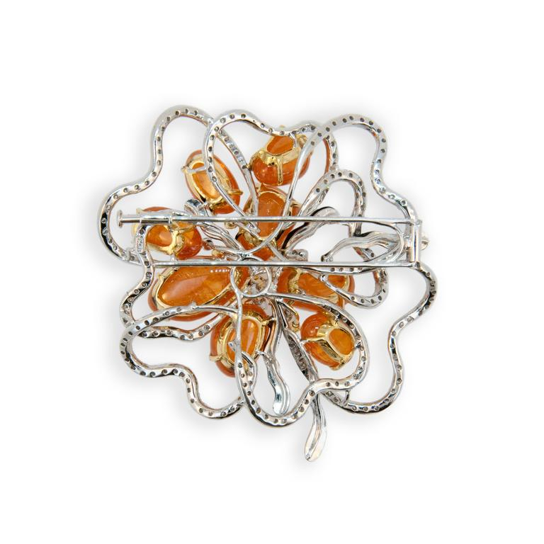 18 karat white and yellow gold brooch set with eight Mandarin Garnets 84.25 carats total weight. 214 Round Diamonds 3.07carat total weight. 8 yellow diamonds .40 carats total weight and five onyx and enamel freeform pieces.