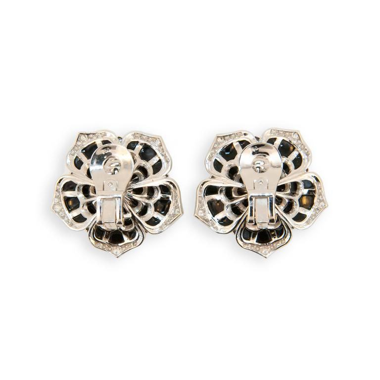 18 karat white gold flower style earrings set with 35 pieces of onyx in each earring 70 total. Edges of petals are set with 150 round diamonds 1.05 carats total weight and center of each flower is set with one rose cut diamond two equal .51 carats