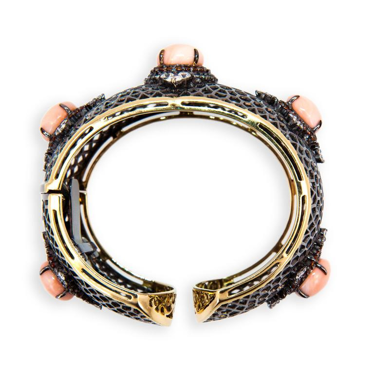 18 karat yellow gold blackened hinged cuff bracelet open web design with five 12.2-12.5 mm Angel Skin Coral Cabs 40.24 carats total weight. 110 Orange Sapphires 3.67 carats total weight. 83 full-cut diamonds 4.51 carats total weight.