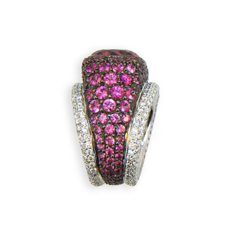 18 karat blackened white gold ring set with a cushion cut Pink tourmaline 12.65 carats total weight 14.68 x 13.72 x 9.36 mm, Surrounded by graduated cut and colored Pink Sapphires 5.86 carats total weight with two rows of diamonds 2.83 carats total