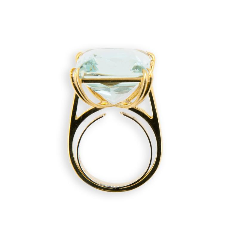 18 karat yellow gold ring set with square Aquamarine 15.21 carats. Double prong on each corner.Size 6 with a horseshoe.