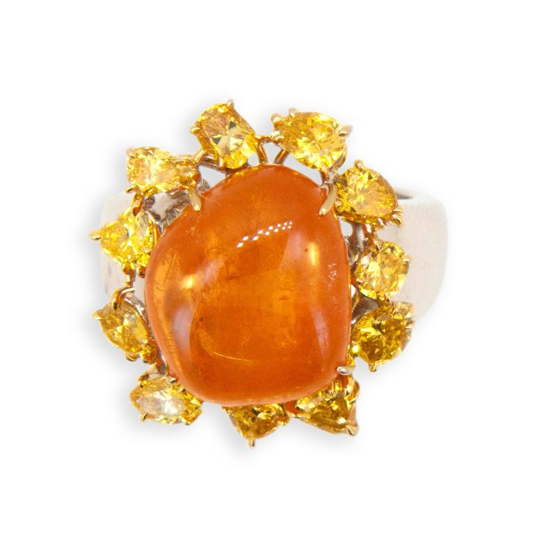 18 karat yellow and white gold ring set with Mandarin Garnet 24.05 carats  total weight.  (11) Fancy shaped yellow diamonds 2.65 carats total weight. Ring is size 7.75 with a horseshoe.