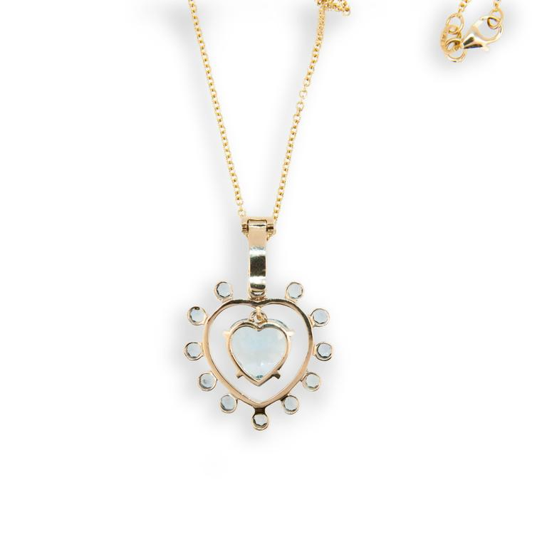 14 karat yellow gold Sweetheart pendant; heart shaped Blue Topaz 5.94 carats surrounded by twelve 2.8 mm round faceted blue topaz  .99 carats total weight round blue topaz. Heart shaped blue topaz swings freely in center. Pendant bail opens and