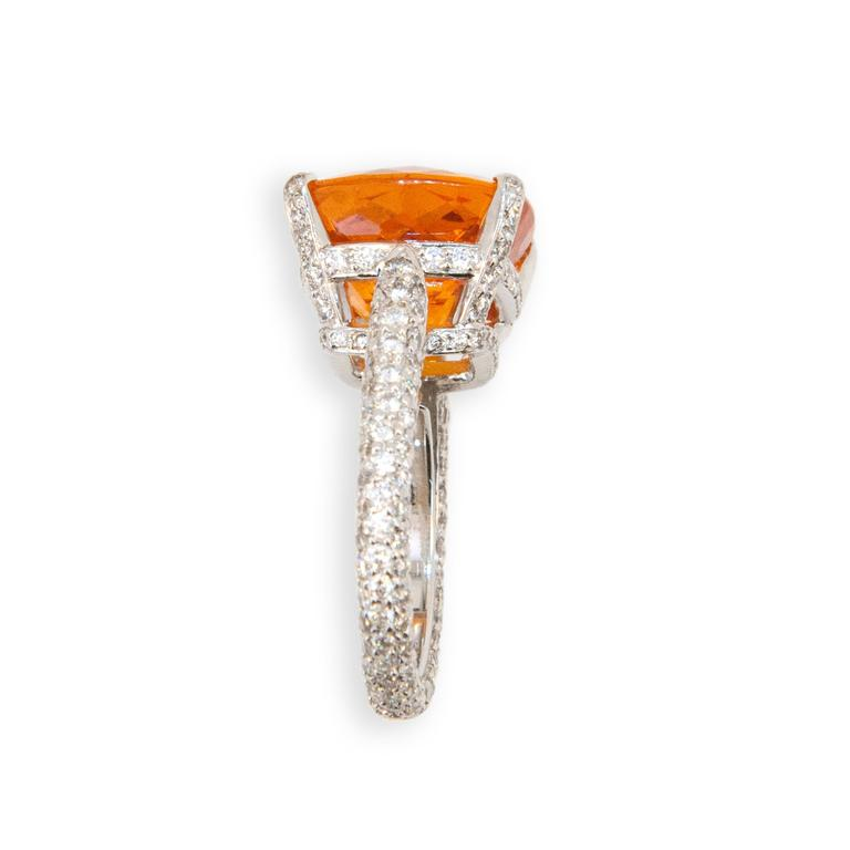 18 karat white gold ring set with one faceted cushion cut Mandarin Garnet 15.10 carats shank, under bezel and prongs are set with 234 round Diamonds 1.94 carats total weight. Ring is a size 6.25 with a horseshoe.