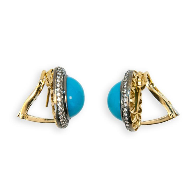 18 karat yellow blackened gold turquoise and diamond earrings. Turquoise approximately 21.29 carats total weight. Diamonds approx. 1.59 carats total weight. Turquoise approximately 15 mm in diameter. Earrings can be worn as pierced or clip on posts