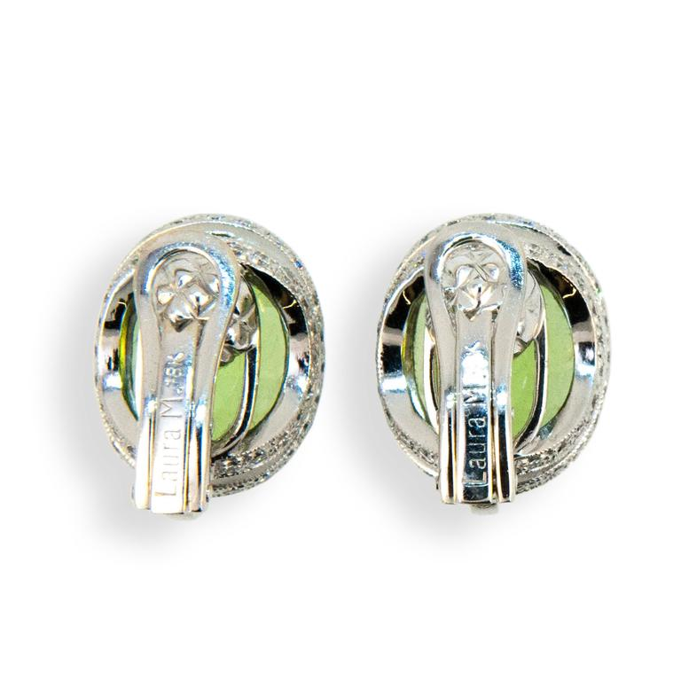18 karat white gold oval checker cut peridot earrings with diamonds. Peridot are 8.65 carats total weight and diamonds 1.20 carats total weight. Earrings are clip on, posts could be added.