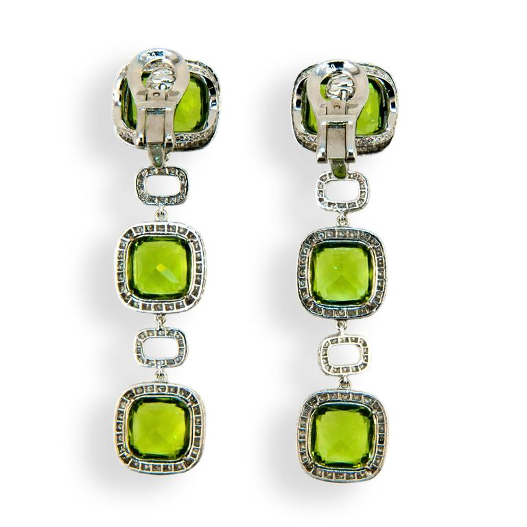 18 karat white gold earring 12 x 10 mm Peridot at top with two 9.5 x 9.5 mm Peridot below 28.90 carats total weight with 542 micro set diamonds surrounding and rectangular diamond sections separating 3.46 carats total weight. Earrings may be worn as