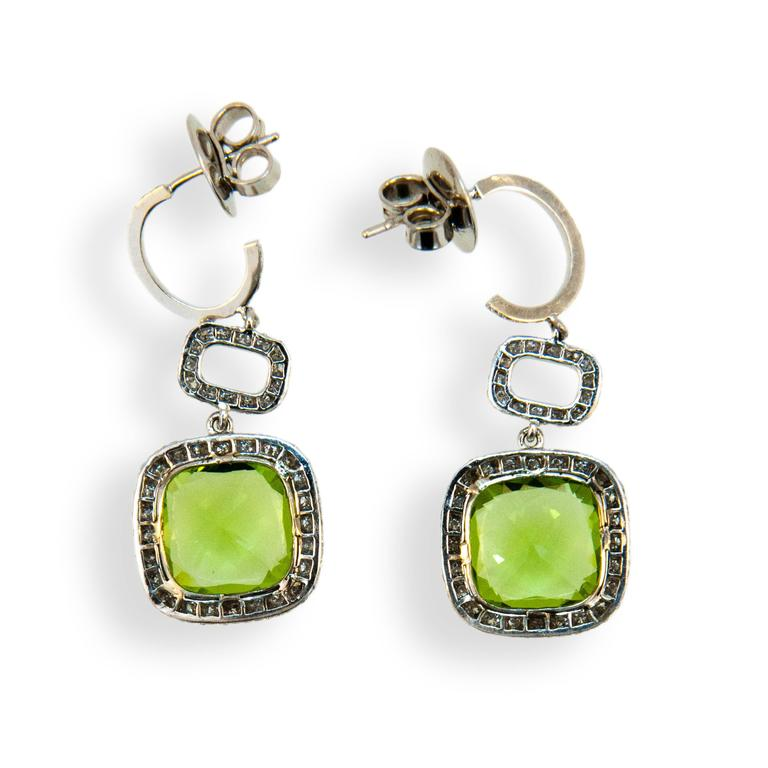 18 karat white gold earrings each set with one 10 x 10 mm cushion cut Peridot 3.36 carats and 3.66 carats. Set in each hoop are (18) diamonds .15 carat total weight. Surrounding Peridot and in connecting link are (85) diamonds 170 total