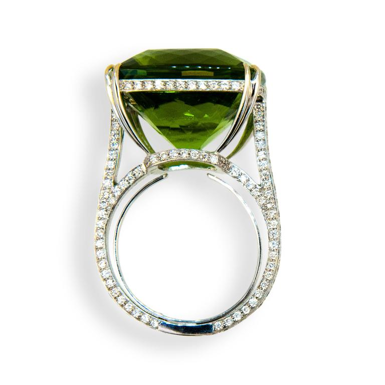 18 karat white gold ring , set in center is one 26.78 carats square faceted cushion cut Peridot. Mounting is set with 226 round diamonds .9-1.4 mm, 1.05 carats total weight. Diamonds are set on under bezel and all sides of shank. Tapered split