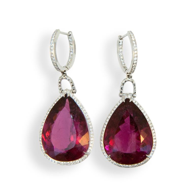 18 karat white gold earrings each set with one faceted pear shaped Rubellite Tourmaline 15.80 carats and 15.65 carats. Diamond hoop is set with (23) diamonds (46) total .19 carat total weight each connecting link is set with (8) diamonds (16) total