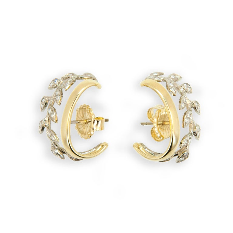 New to the Laura Munder Collection! 18 karat yellow and white gold leaf hoop earrings each set with 23 round 1.2 - 1.3 mm full cut diamonds H/SI-1 approximately .45 carat total weight.