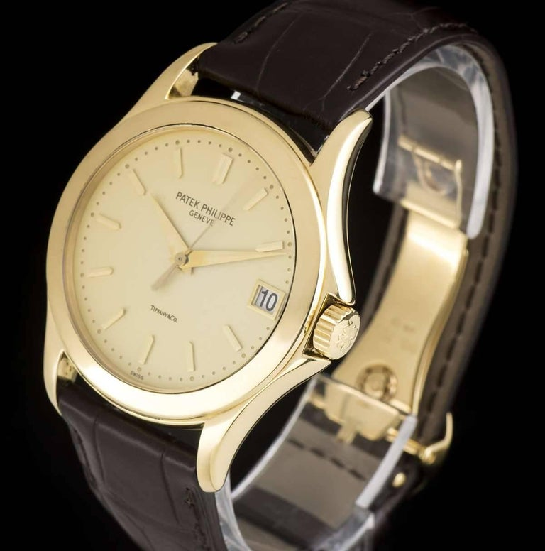 An 18k Yellow Gold Double Name Calatrava Gents Wristwatch, opaline silver dial (retailed by Tiffany & Co) with applied index batons, date at 3 0'clock, a fixed 18k yellow gold bezel, a brand new original brown leather strap with an original 18k