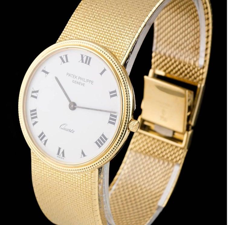 An 18k Yellow Gold Calatrava Vintage Gents Wristwatch, white enamel dial with roman numerals, a fixed 18k yellow gold hobnail bezel, an 18k yellow gold integrated bracelet with an 18k yellow gold jewellery style clasp, sapphire glass, quartz