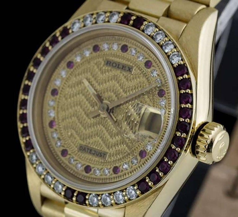 An 18k Yellow Gold Oyster Perpetual Datejust Ladies Wristwatch, rare champagne decorated string dial set with 22 round brilliant diamonds and 11 rubies, date at 3 0'clock, a fixed 18k yellow gold bezel set with 24 rubies and 16 round brilliant