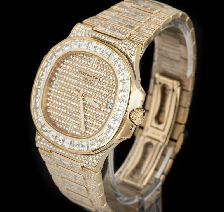 An rare, specially made piece by Patek Philippe, unworn 18k Rose Gold Fully Loaded Nautilus Gents Wristwatch, pave diamond dial set with approximately 255 round brilliant cut diamonds (~1.36ct) and 3 baguette cut hour markers (~0.01ct), date at 3