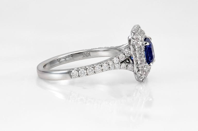 Features a beautiful 1.18 carat blue sapphire at the center. Framed by 2 rows of brilliant round diamonds. Diamonds also set half way all over the shank of ring. Weight of the diamonds is 0.70 carats. Made in 18k white gold. Size 6 US