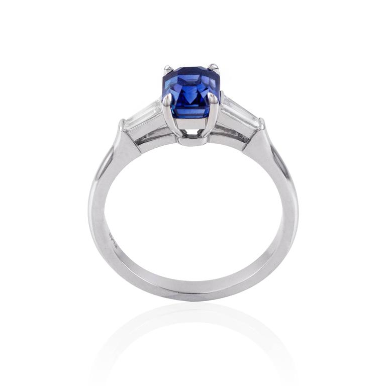 Wonderful emerald cut blue sapphire weighing 1.78 carats. The sapphire has a deep royal blue color and is eye clean. The ring has 2 baguette diamond side stones weighing 0.26 carats total. Made with platinum. Size 6 1/4 (sizable).   Style available