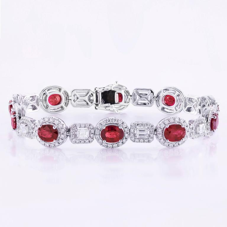 Gorgeous tennis bracelet set with rubies alternating with emerald cut diamonds. Total weight of the rubies is 7.00 carats; Total weight of the emerald diamonds is 1.36 carats. Each ruby and emerald diamonds is accented by a single row of round
