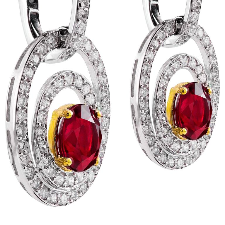 These pair of earrings feature 2 oval cut rubies weighing 2.67 carats total surrounded by 2 rows of brilliant white diamonds that continue on to hinged earwire. Set in 18k gold.  Style available in different price ranges. Prices are based on your