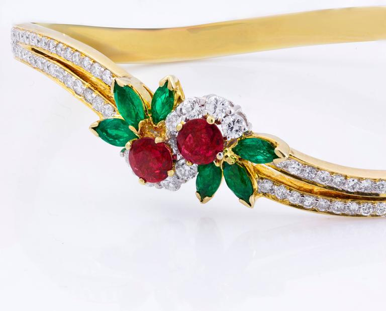 This beautiful bracelet is an estate piece that features 2 rubies weighing 0.80 carats total accented with brilliant round diamonds around. Set with marquise cut emeralds weighing 1.20 carats total on each side of the emerald. Looks like a flower