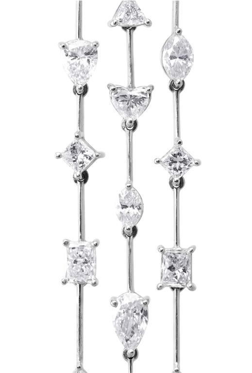 Each earring features 3 columns set with different fancy cut diamonds. Total weight of the diamonds is 9.15 carats. The diamonds range from F-G color and VS-SI1 clarity. Made with 18k white gold. Has post.