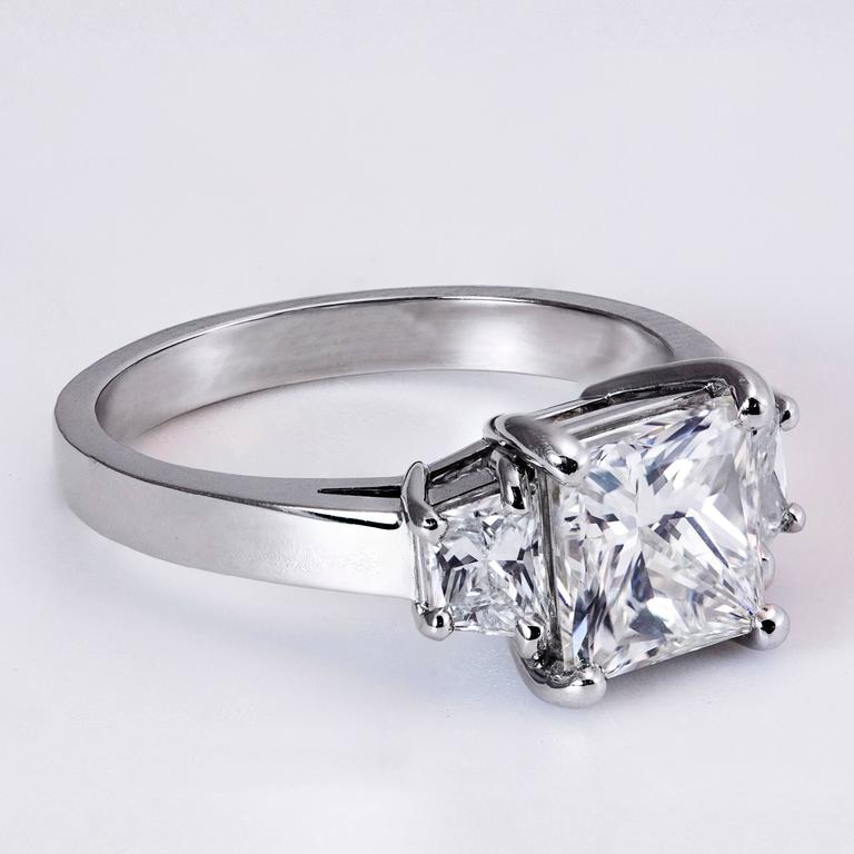 This ring is set with a 2.01 carat princess cut diamond center stone that GIA certified as I color and VS2 clarity. Accented with a trapezoid cut diamond on each side weighing 0.49 carats total. Made in Platinum. Size 6.5 US (sizable).  Style